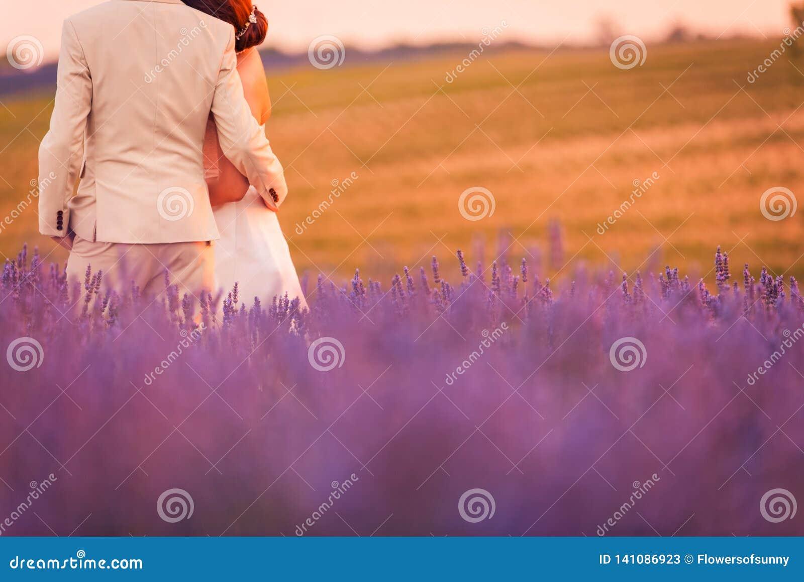Paar op lavendelgebied, romantische zonsondergang en mooie aardachtergrond De idyllische bestemming van het huwelijkspaar, de scè