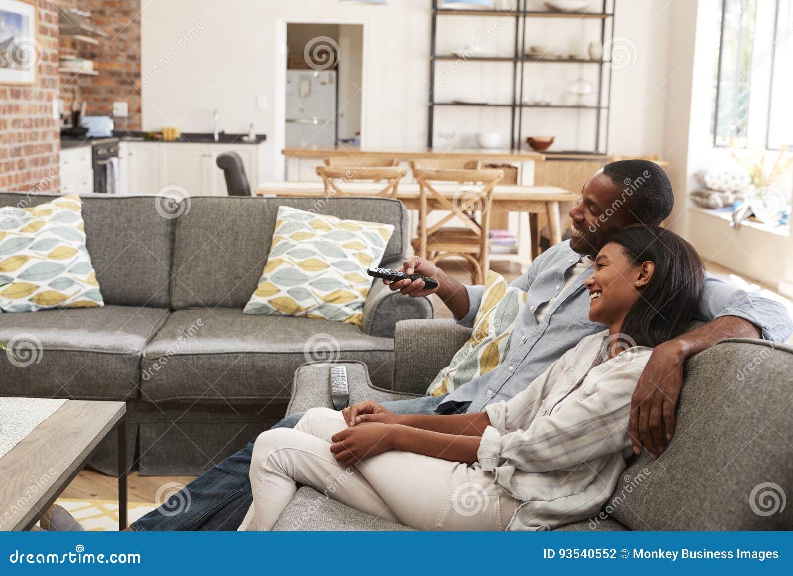 Paar-Sit On Sofa In Open-Plan-Aufenthaltsraum-aufpassendes Fernsehen