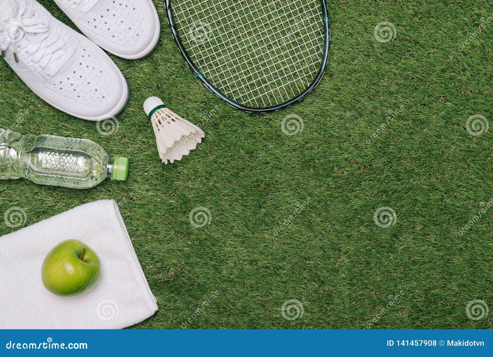 Paar sportschoenen, verse appel en toebehoren voor sport op groen gras, gezonde en actieve levensstijlen, exemplaarruimte voor te