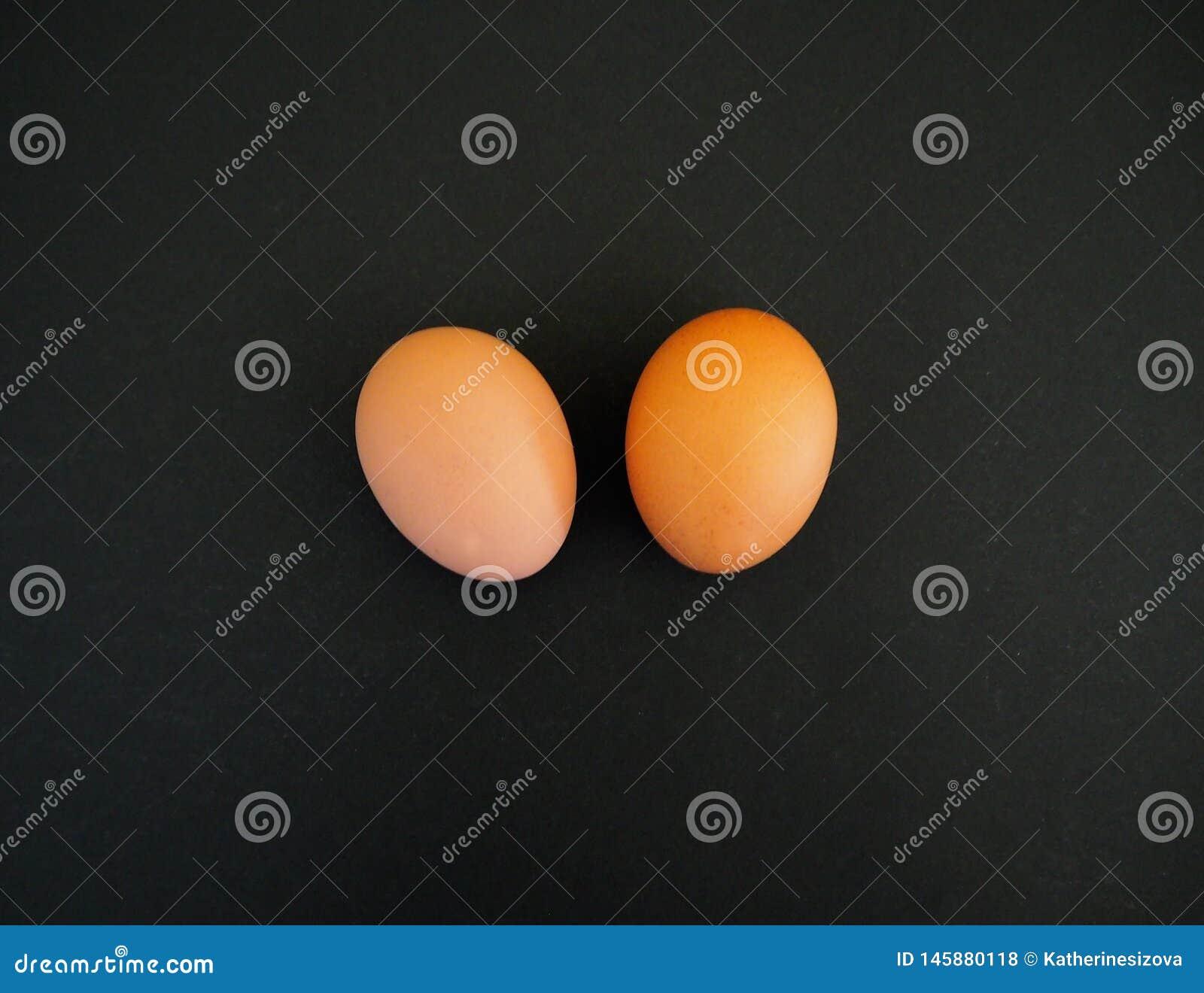 Paar van bruine eieren op de zwarte achtergrond