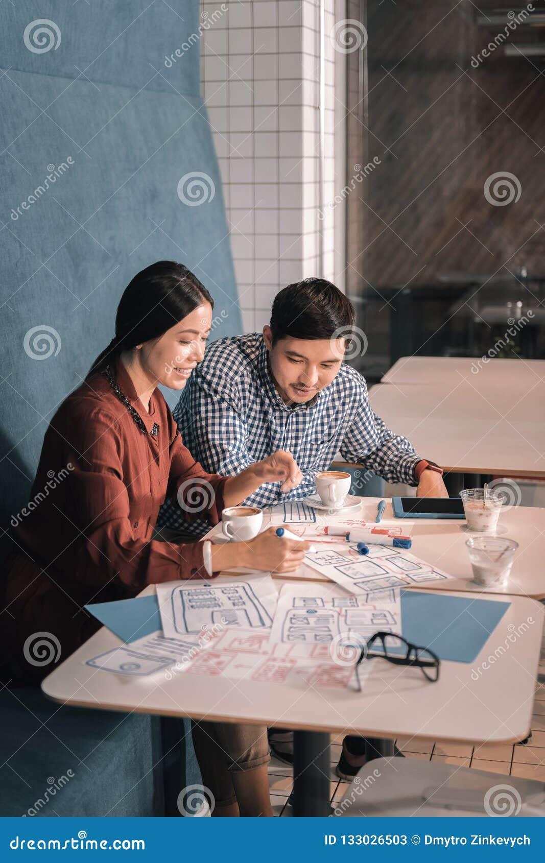 Paar van leuke houdende van zakenlieden die in cafetaria samenwerken