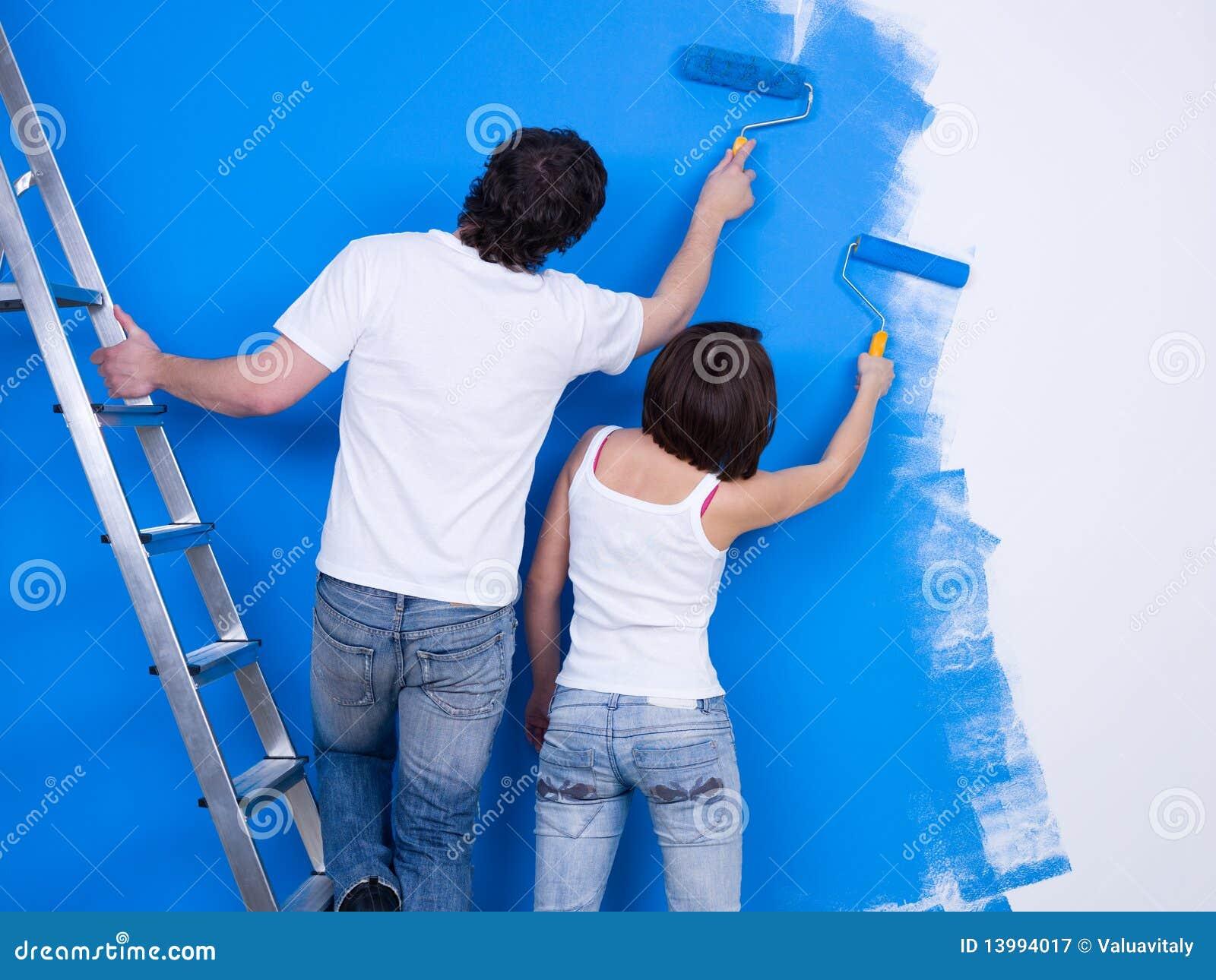 Paar Van Mensen Die De Muur Schilderen Stock Afbeelding