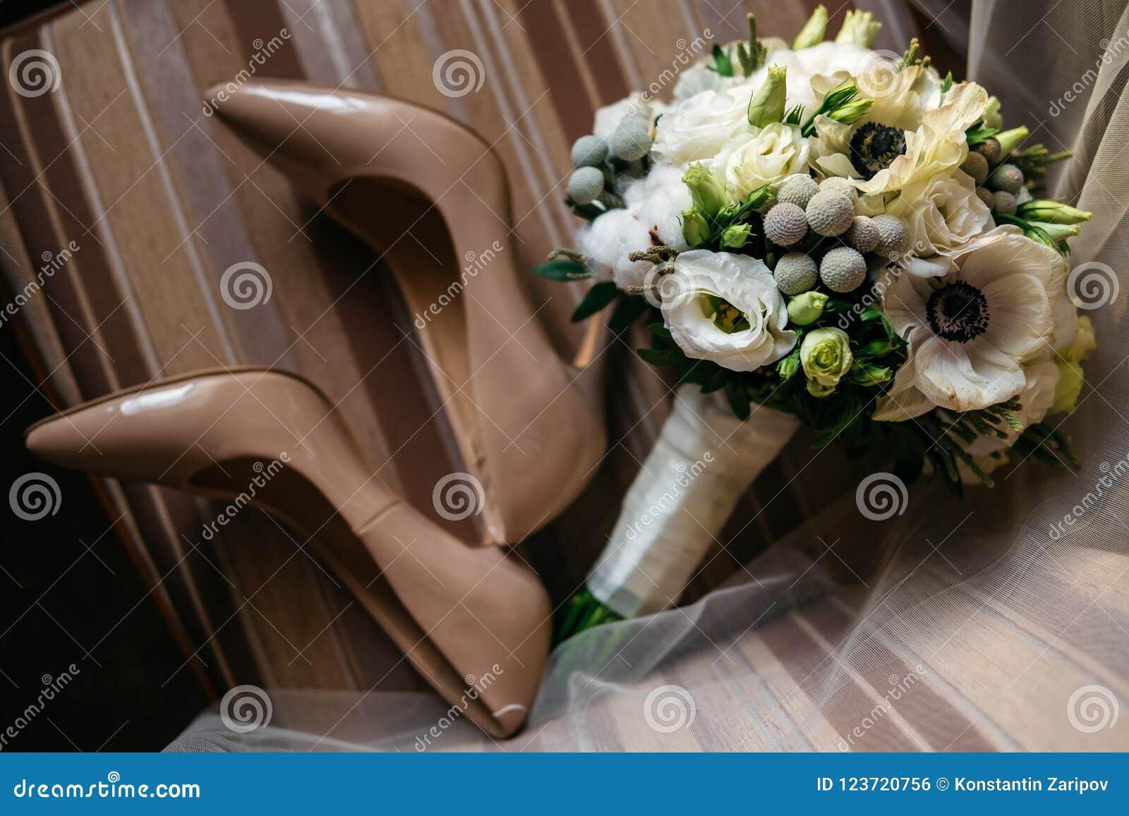 Paar van mooi vrouwen` s schoenen en boeket van bloemen