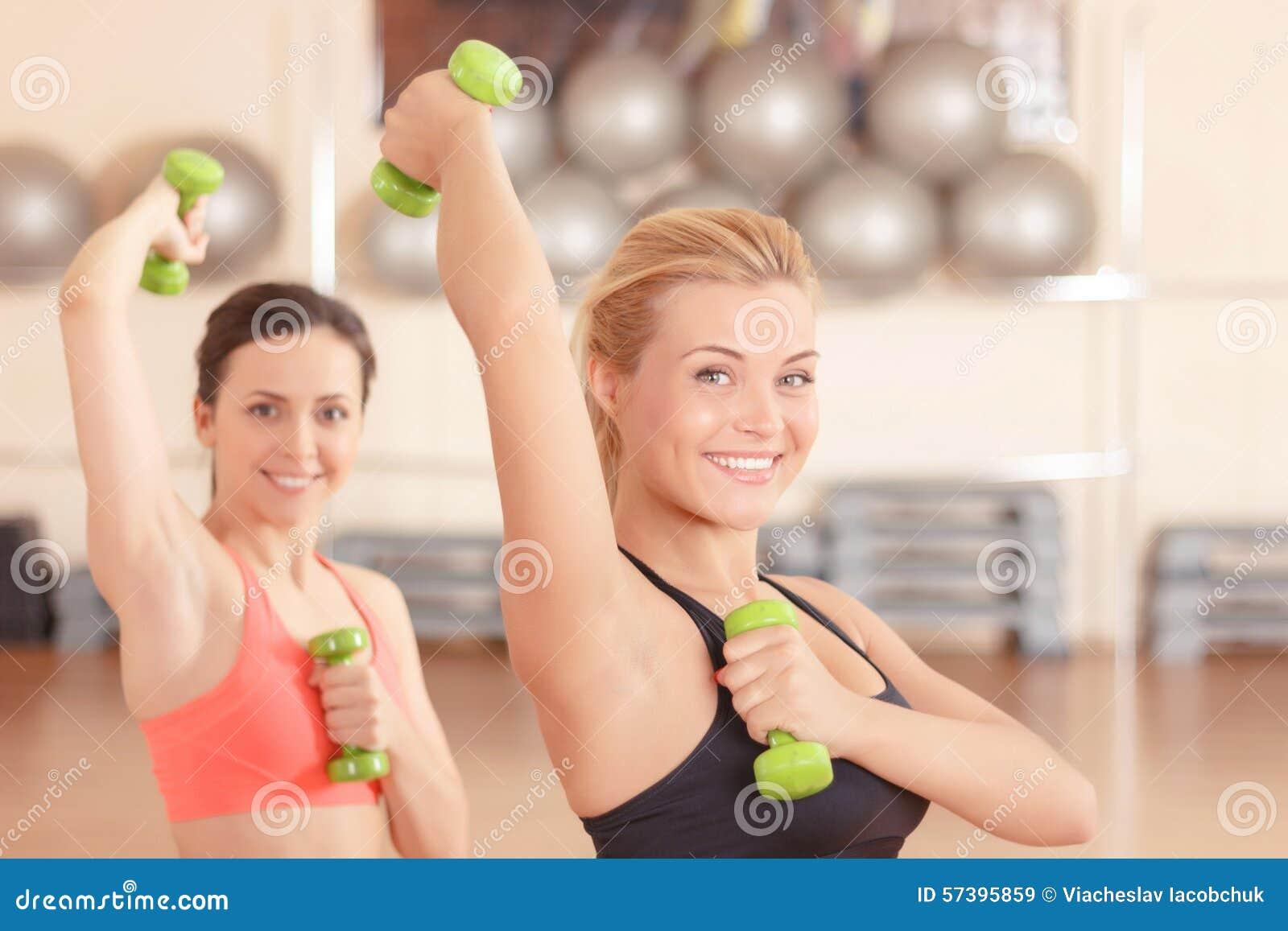 Paar vrouwen die gewichtengeschiktheid doen