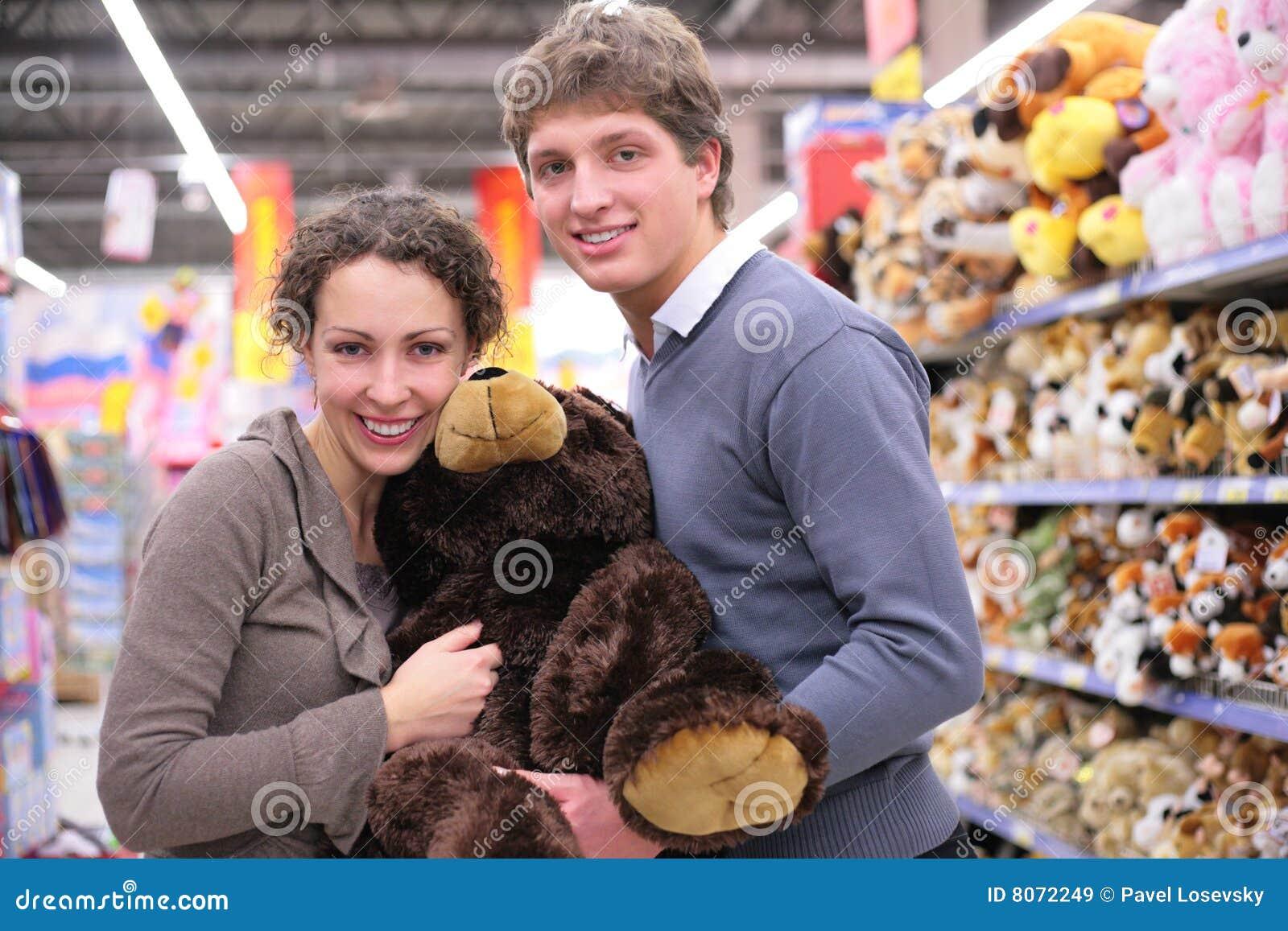 Paar in winkel met zacht stuk speelgoed