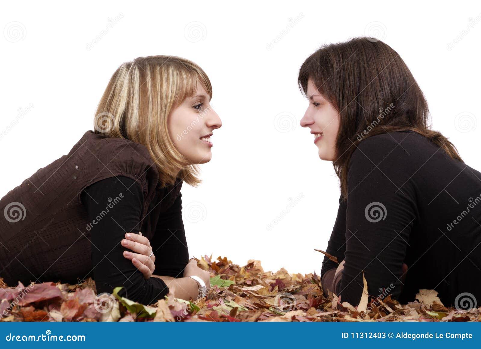 Paare der jungen girlfiends, die in den Herbstblättern liegen