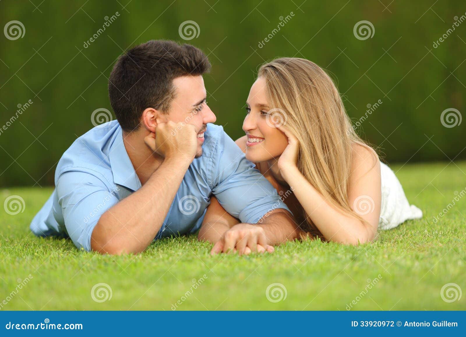 Paare in der Liebe, die liegend auf dem Gras datiert und sich schaut