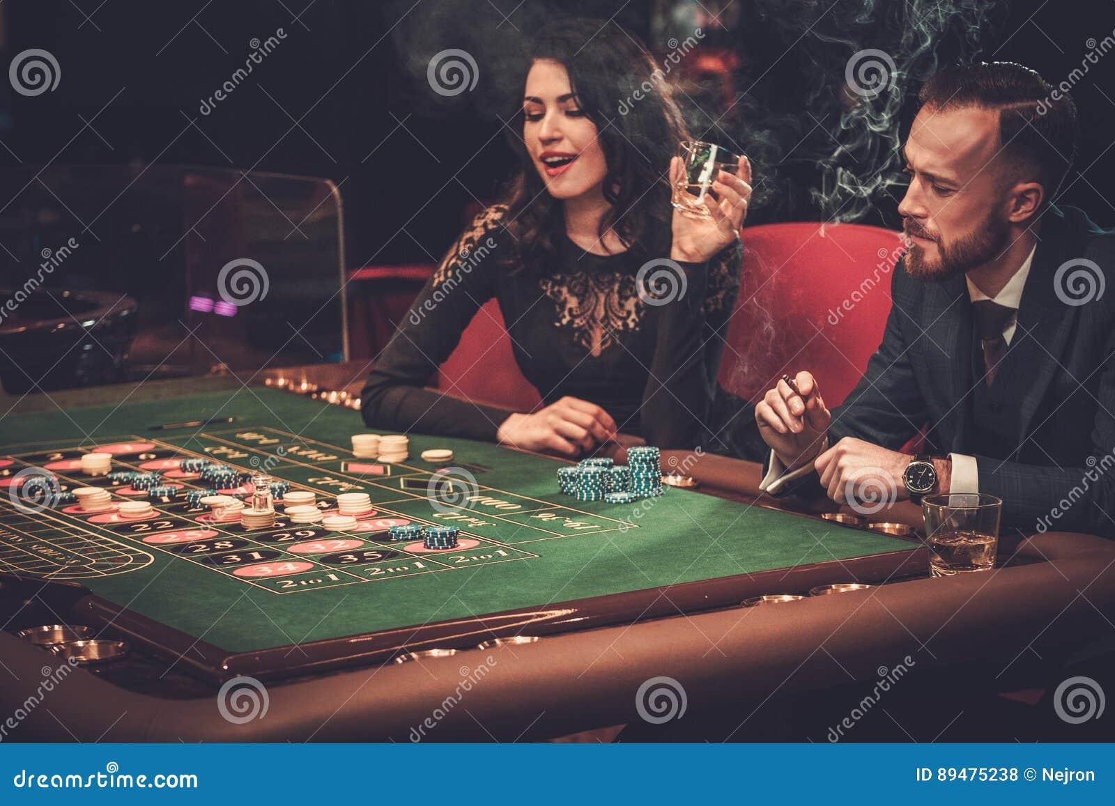Paare der oberen Klasse, die in einem Kasino spielen