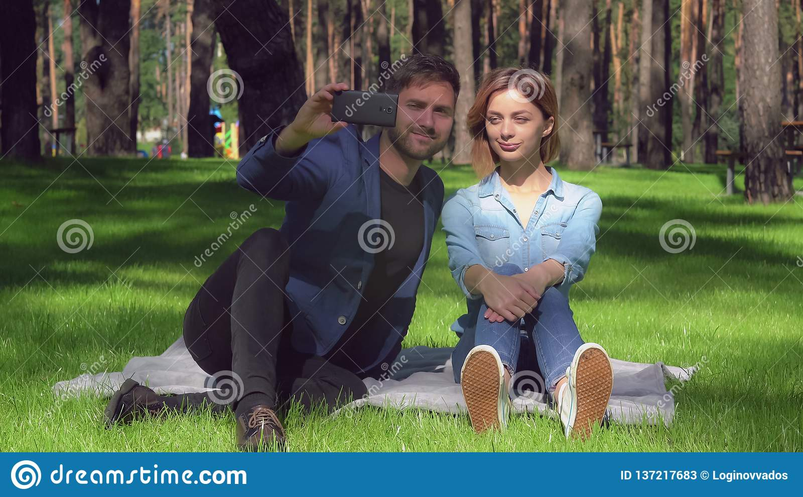 Paare in der zufälligen Kleidung, die Fotogebrauch Smartphone nimmt
