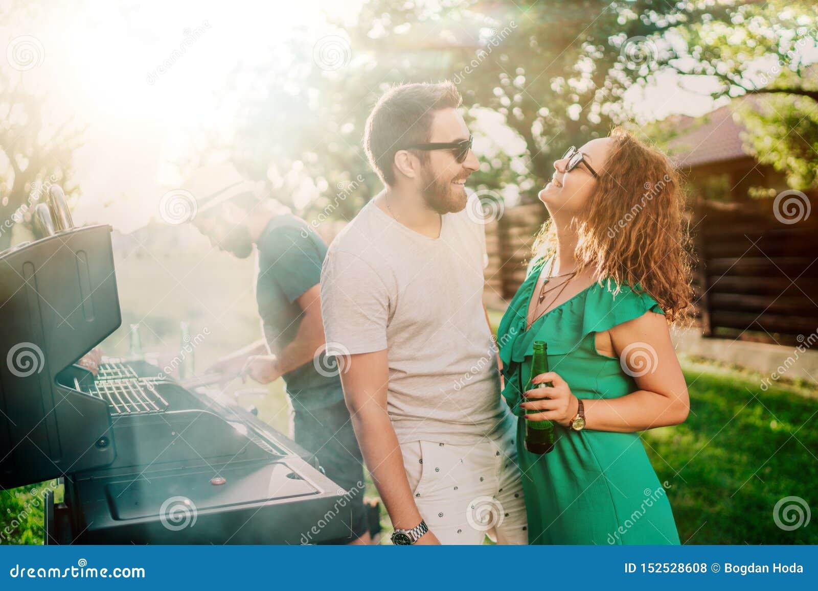 Paare, die über bbq-Partei genießt Getränke und hat eine gute Zeit lachen Gartenkochen im Freien