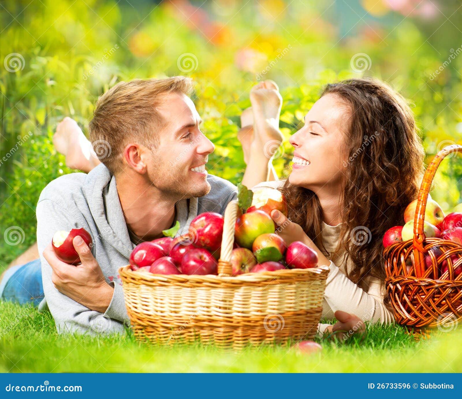 Paare, die auf dem Gras sich entspannen und Äpfel essen