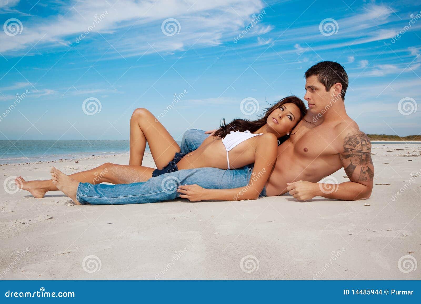 Paare, die auf einem Strand liegen
