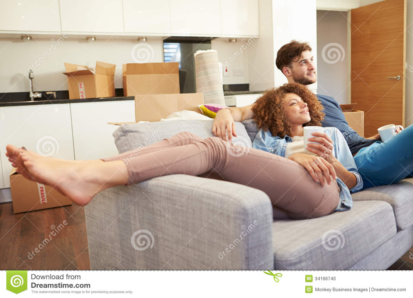 Paare, die auf neuem Haus Sofa With Hot Drink Ins sich entspannen