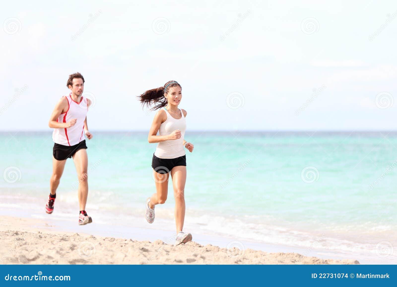 Paare, die auf Strand laufen