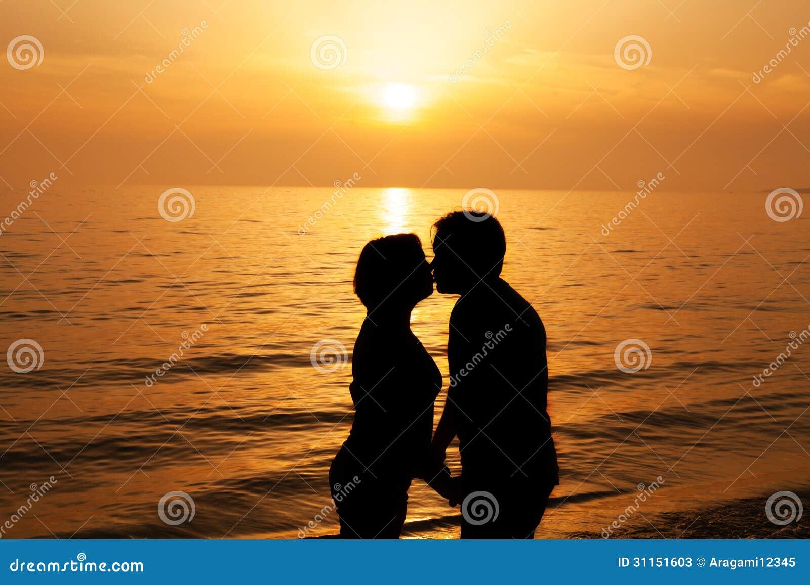 Paare die bei sonnenuntergang auf der küste küssen