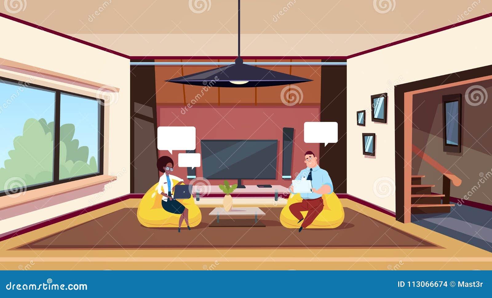 Paare, die an Computern Sit In Bean Bag Chairs im modernen Wohnzimmer arbeiten