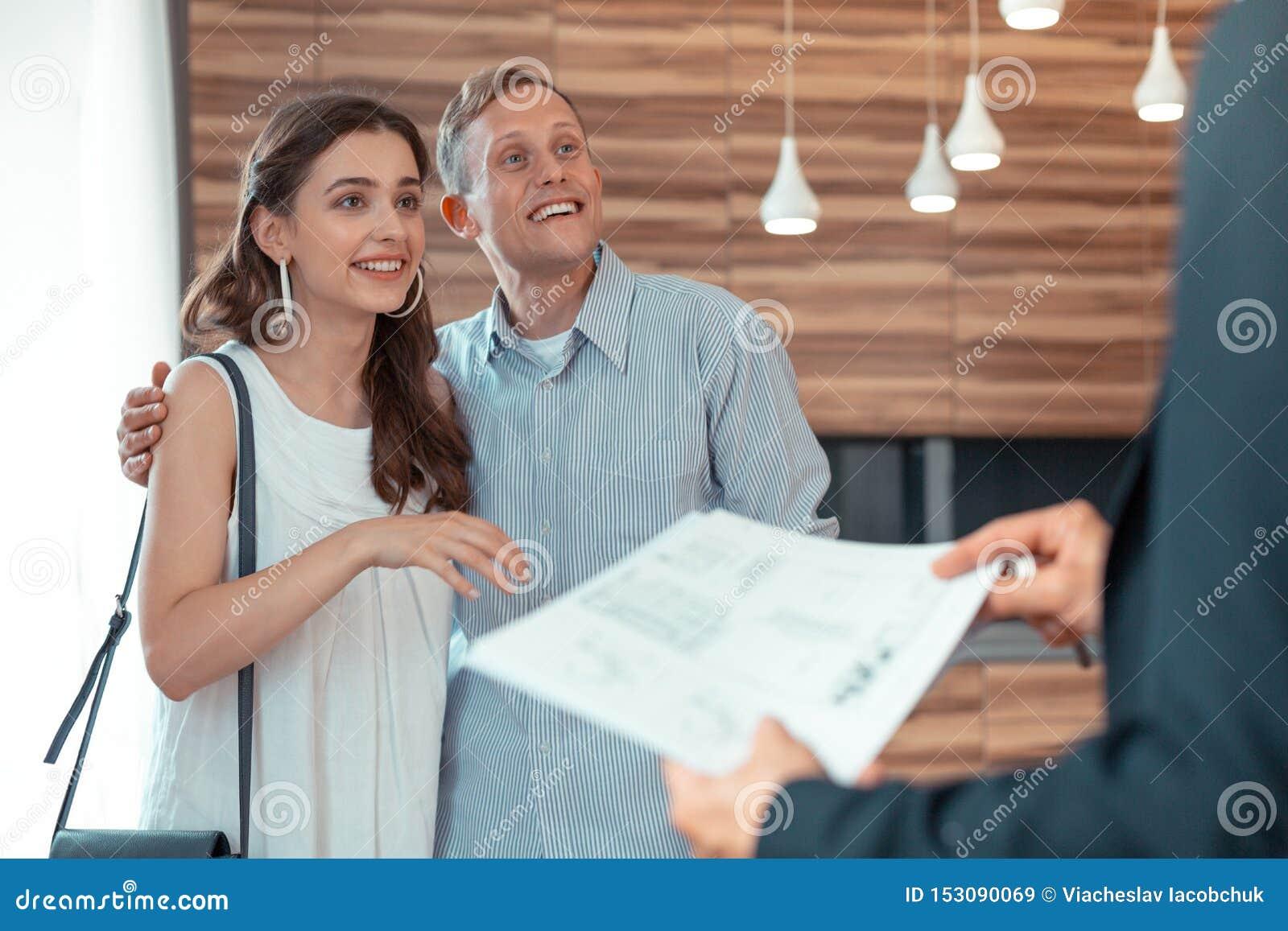 Paare, die den Grundstücksmakler gibt ihnen die Dokumente betrachten