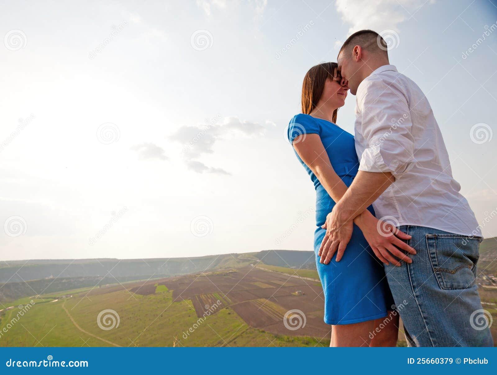 Paare, die in der Landschaft umarmen