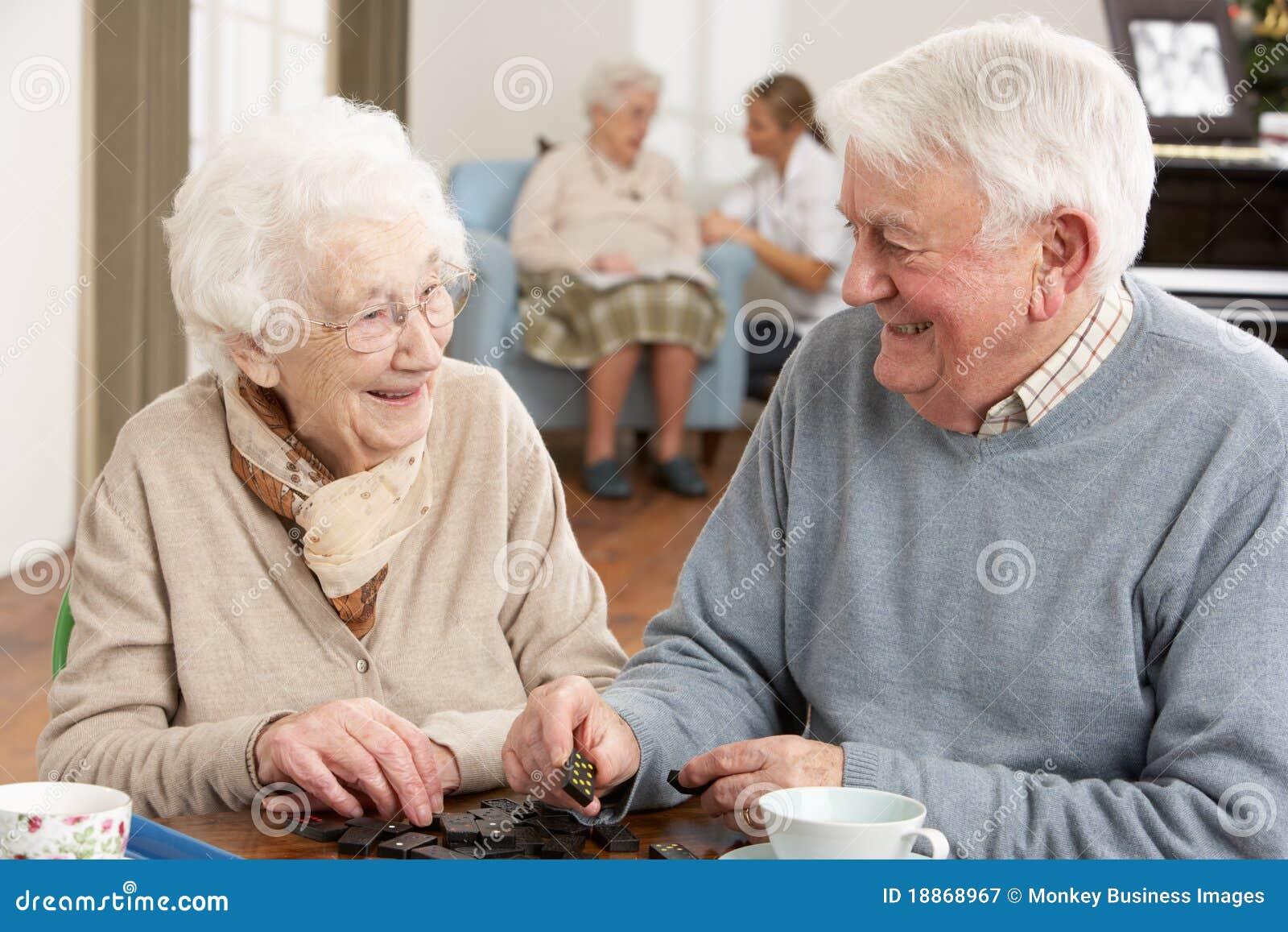 Paare, die Dominos in der Tagesbetreuung-Mitte spielen