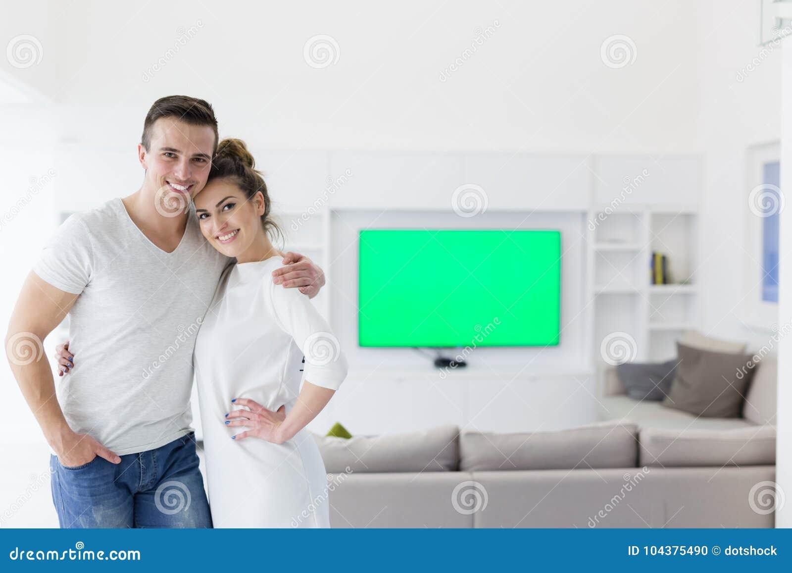 Paare, die in ihrem neuen Haus umarmen