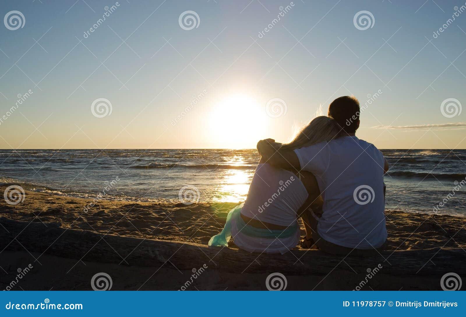 Paare, die nahe dem Meer auf Sonnenuntergang sitzen