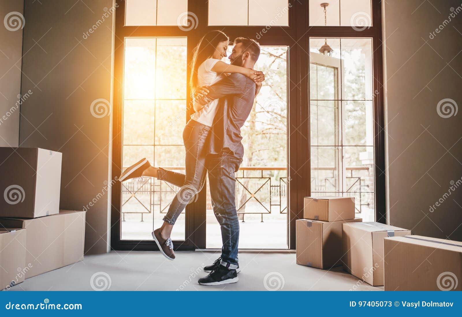 Paare, die in neues Haus sich bewegen