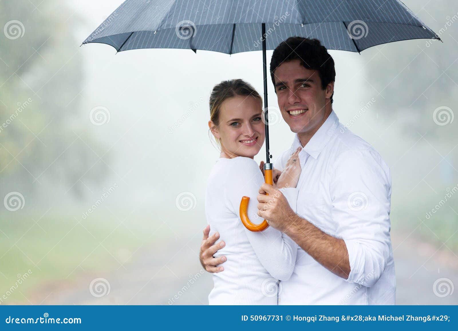 Paare, die Regenschirm halten