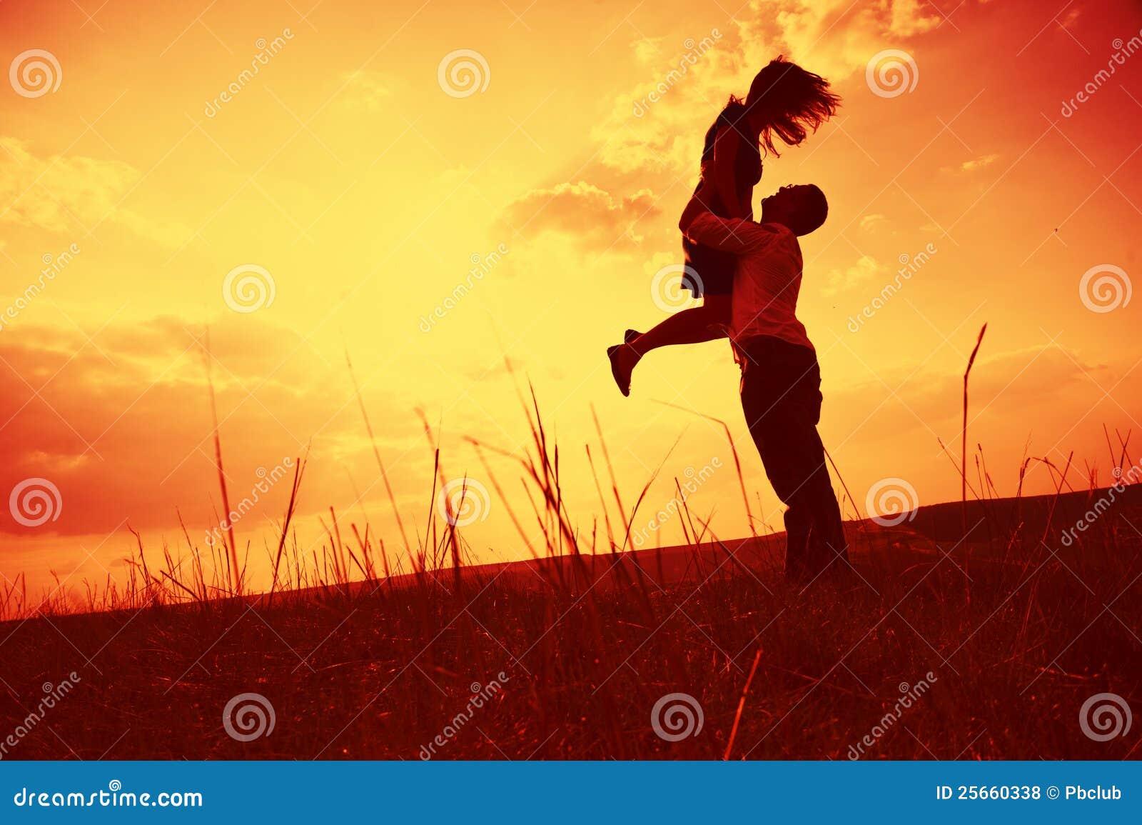 Paare, die am Sonnenuntergang umfassen