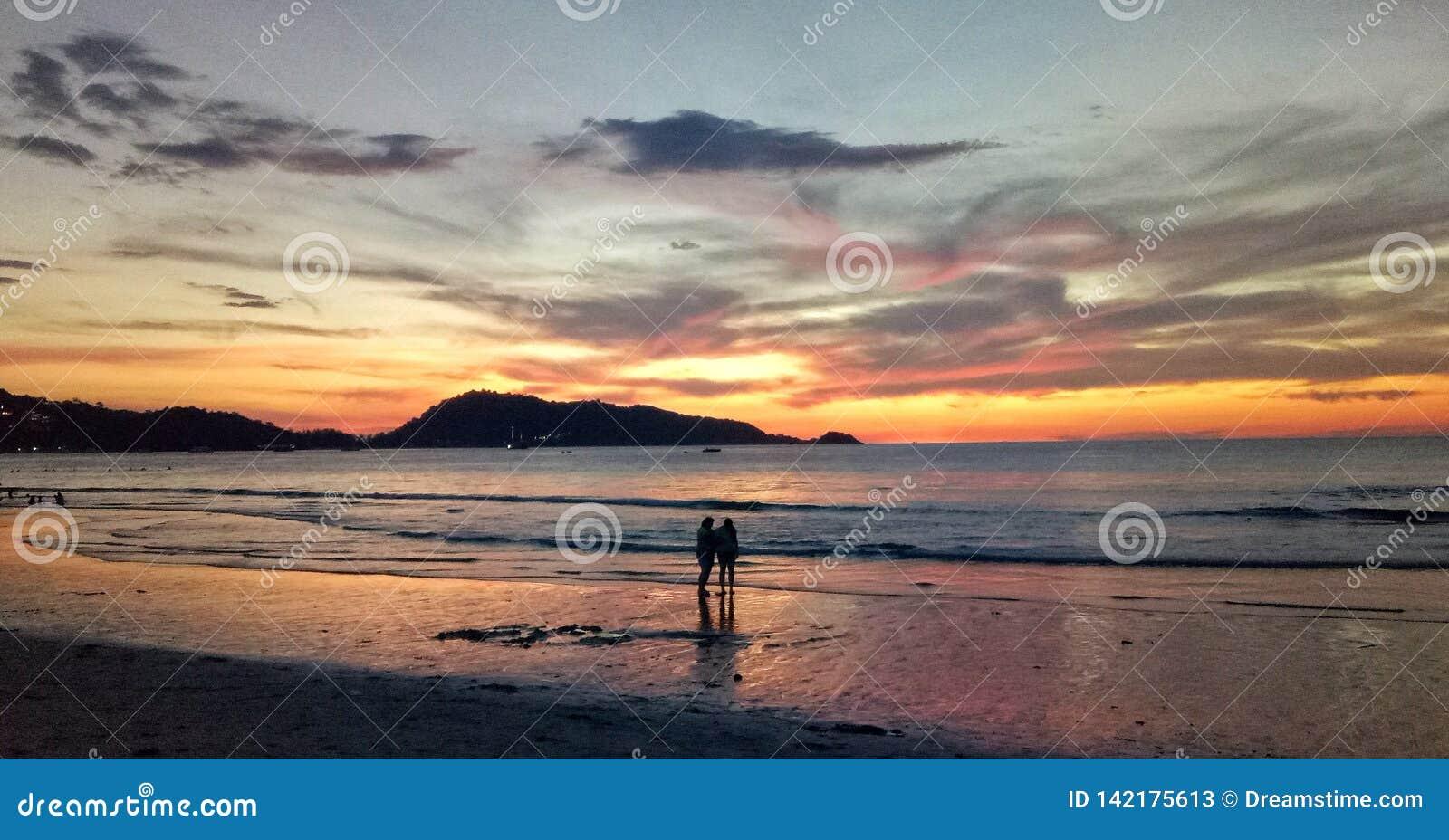 Paare, die unter Sonnenuntergang stehen