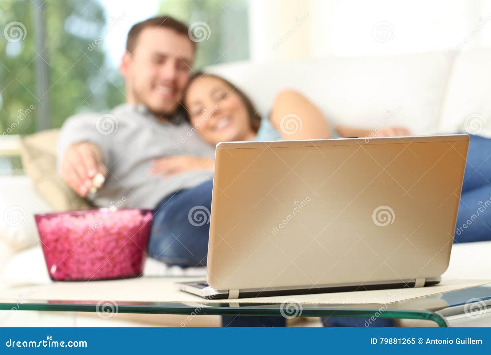 Paare, die zu Hause in einem Laptop fernsehen