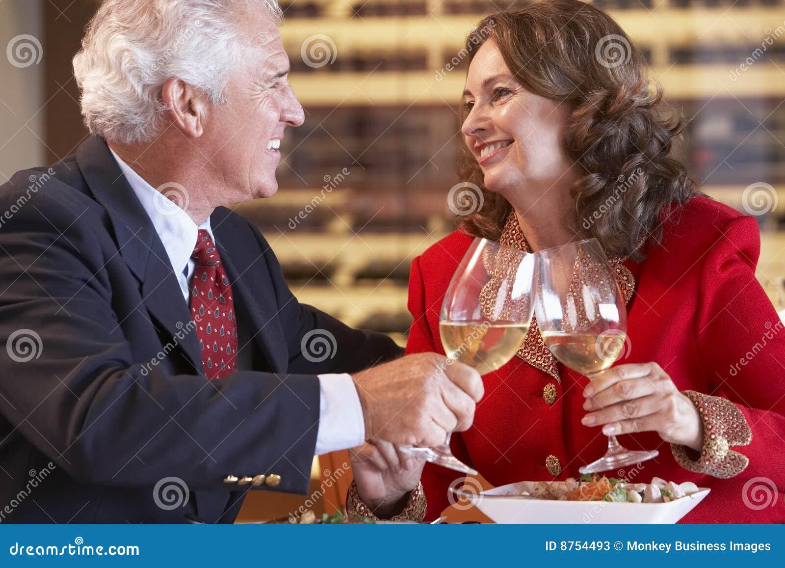 Paare, die zusammen Abendessen essen und Wein trinken