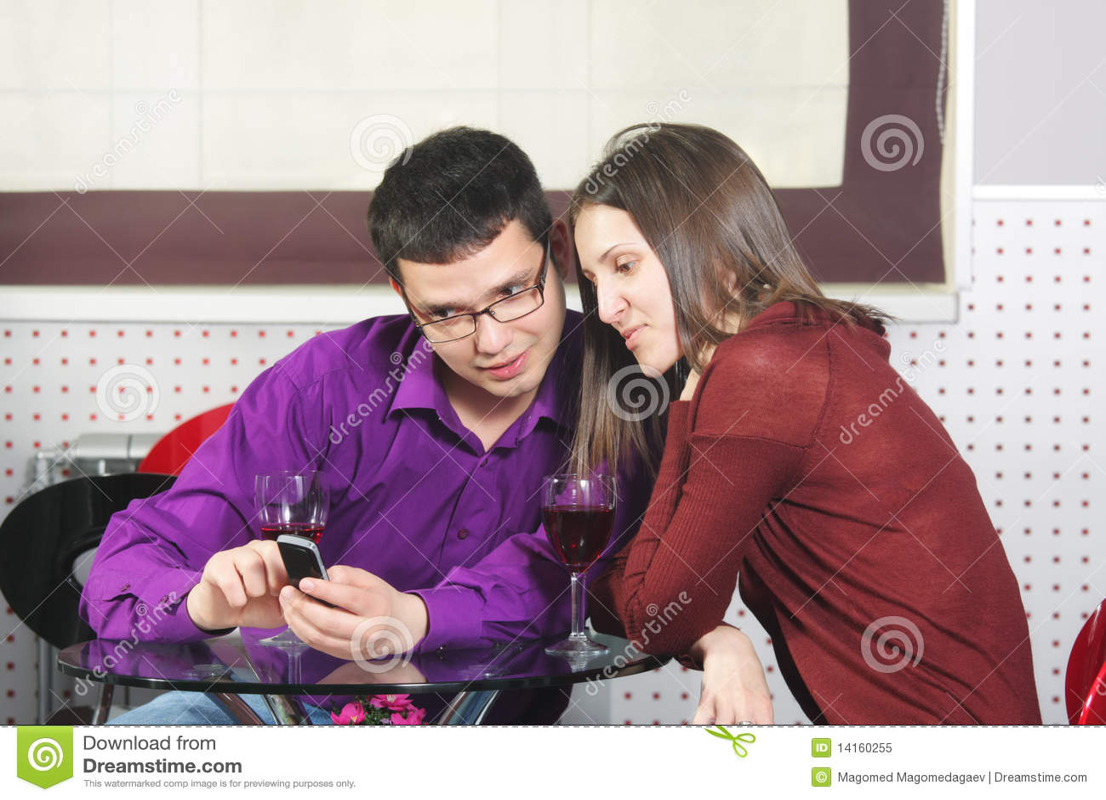 Paare im Kaffee, der Mobiltelefon betrachtet