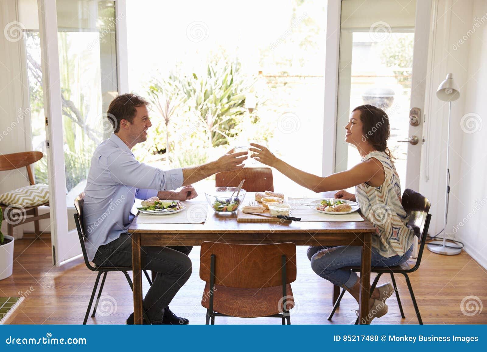 Paare machen einen Toast, während sie Mahlzeit zu Hause zusammen genießen