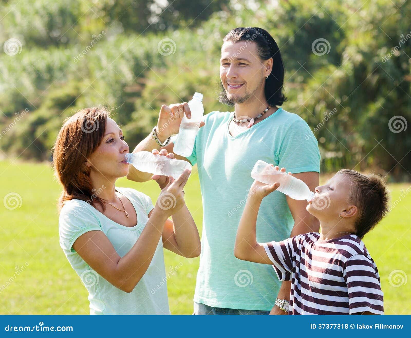 Paare mit Trinkwasser des Jugendlichen von den Flaschen