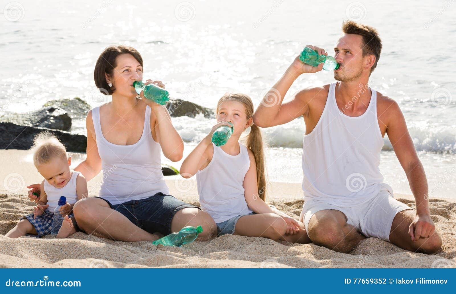 Paare mit zwei Kindern, die Süßwasser auf sandigem Strand trinken