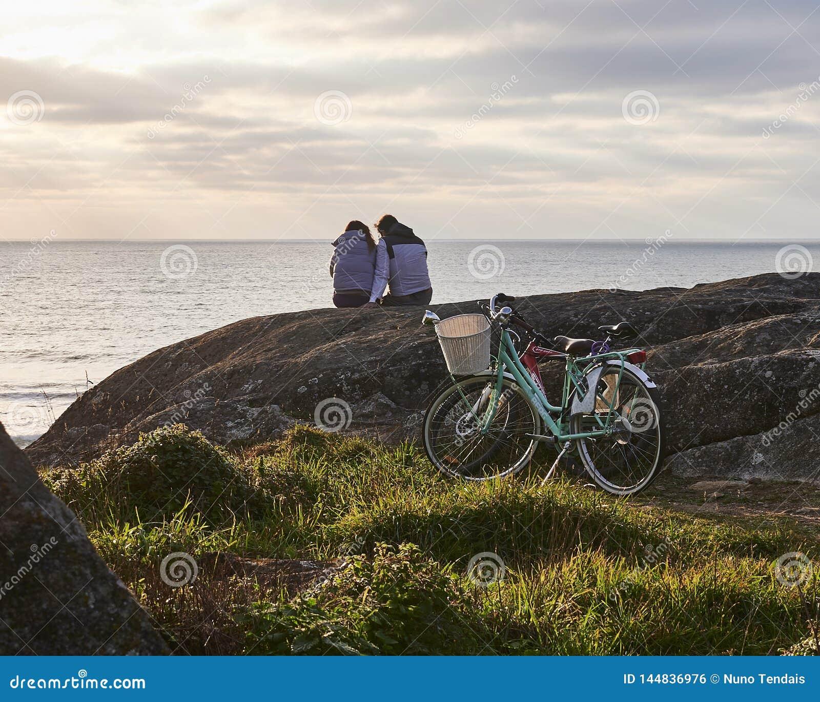 Paare passen den Sonnenuntergang nach Fahrradfahrt auf