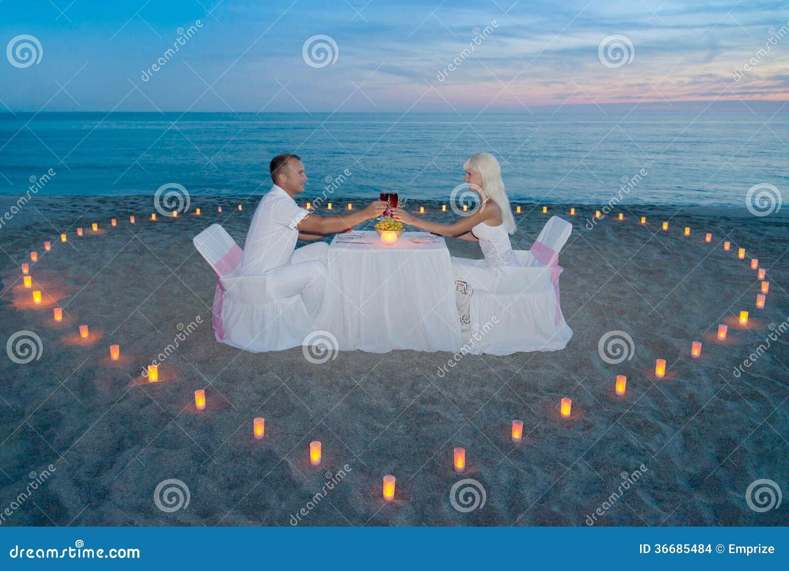 Paare am romantischen Abendessen des Strandes mit Kerzenherzen