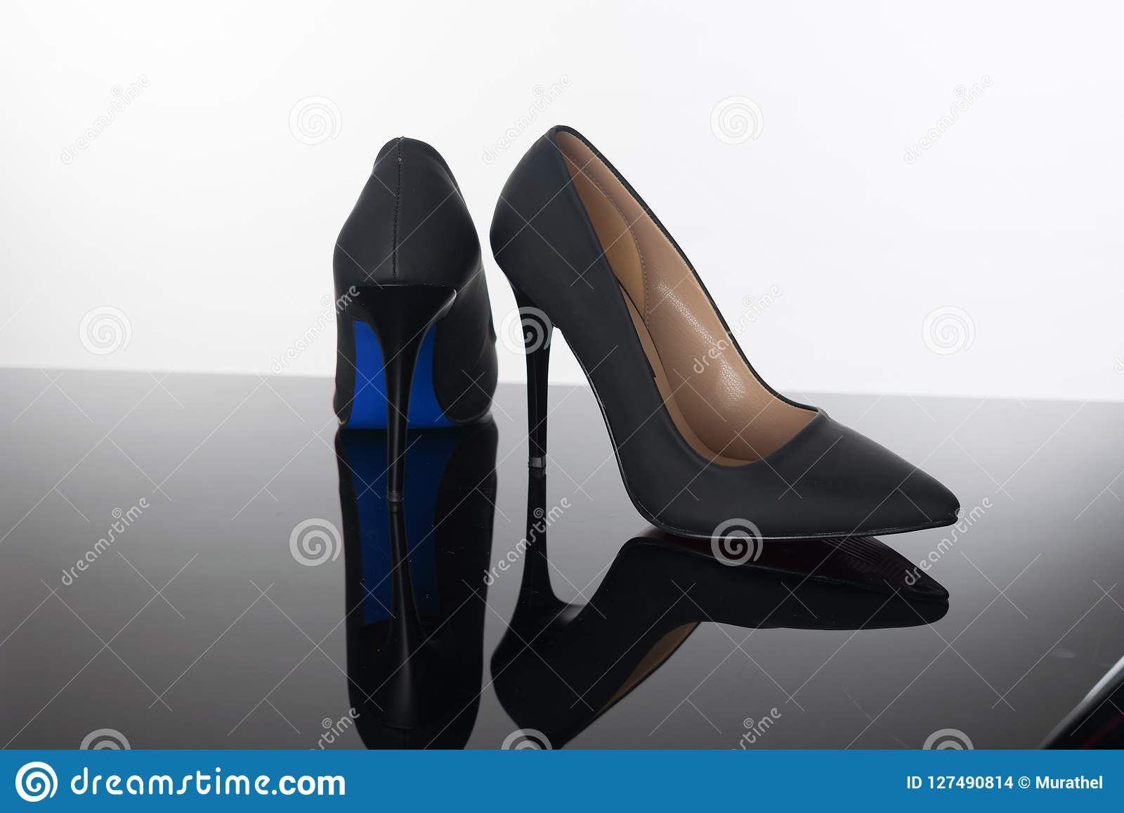 97af420a5a9c7a Paare Schuhe der spitzen Frau mit blauen hohen Absätzen der Seezungen auf  reflektierendem Boden