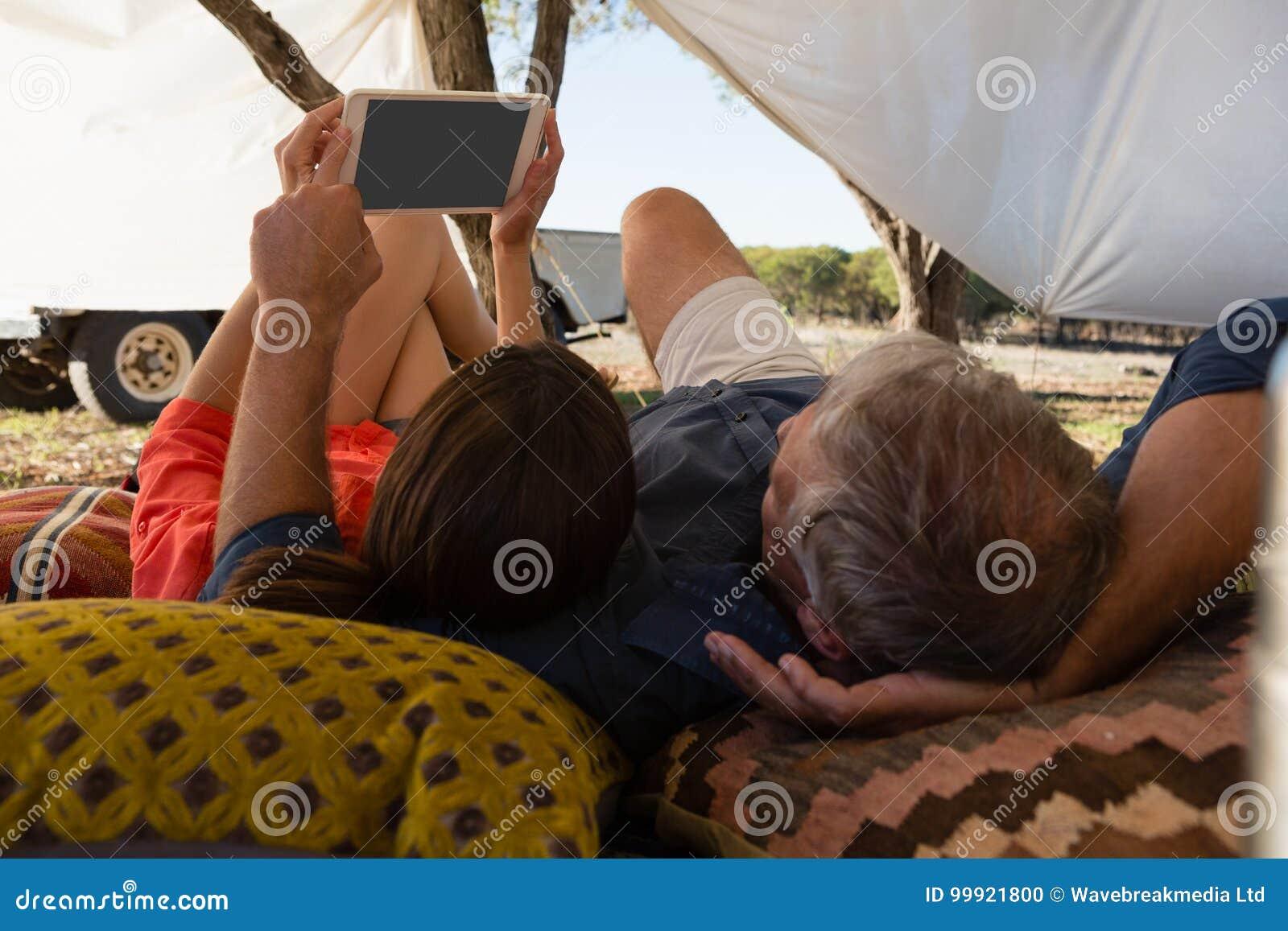 Paare unter Verwendung der Tablette im Zelt