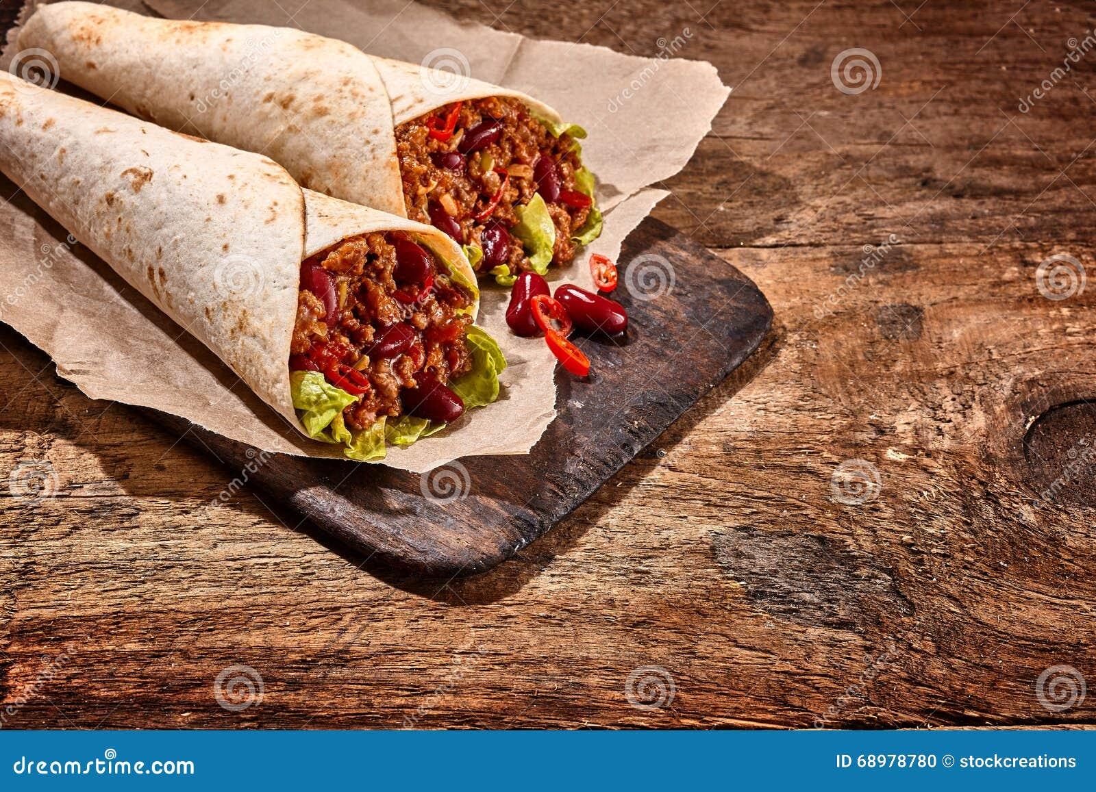 Paare von Chili Stuffed Tex Mex Wraps auf hölzerner Tabelle