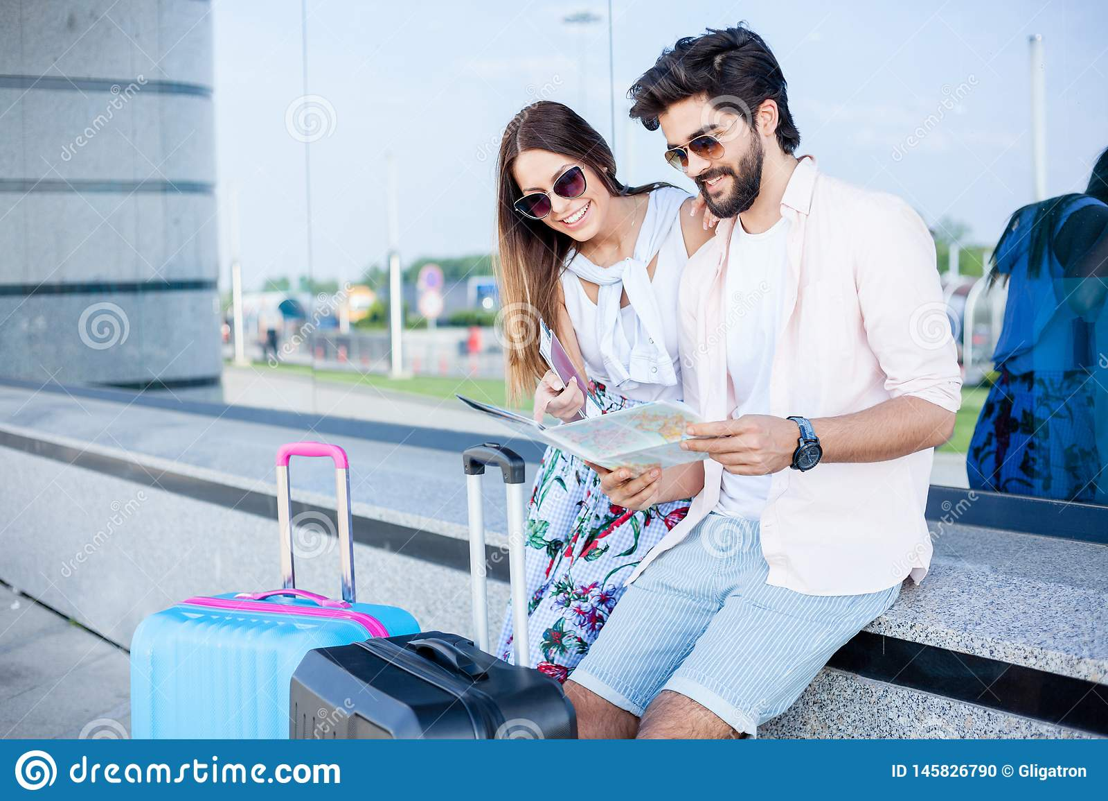 Paare von den jungen Touristen, die vor einem Flughafenabfertigungsgeb?udegeb?ude sitzen und die Karte betrachten