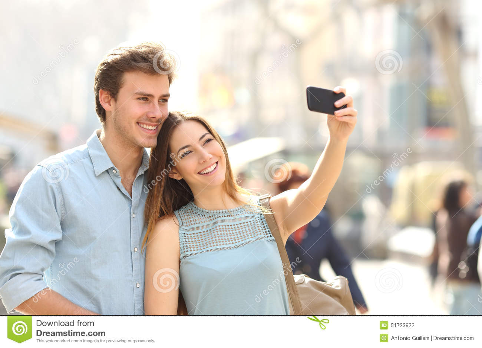 Paare von den Touristen, die ein selfie in einer Stadtstraße fotografieren