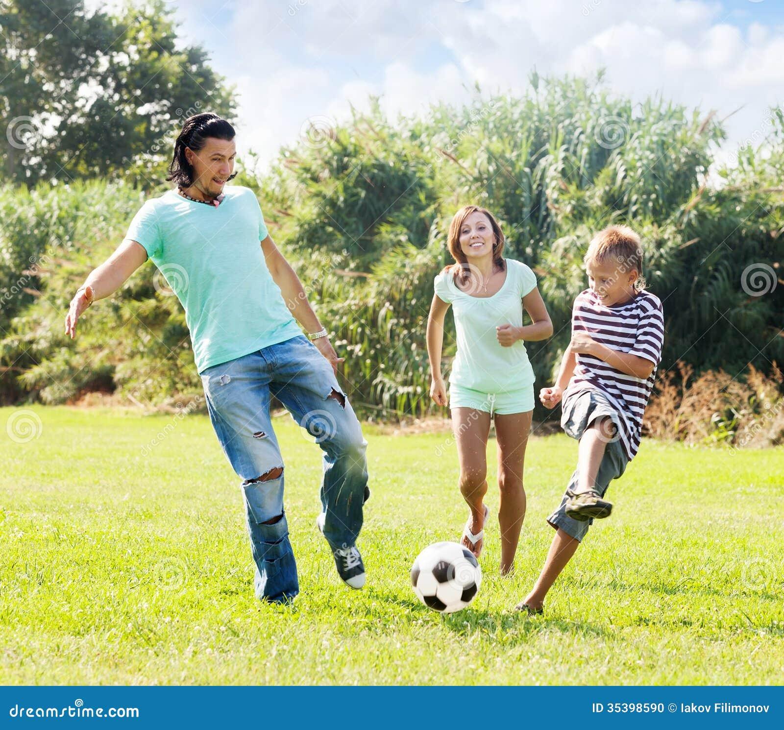 Paare von mittlerem Alter und Jugendlicher, die mit Fußball spielt