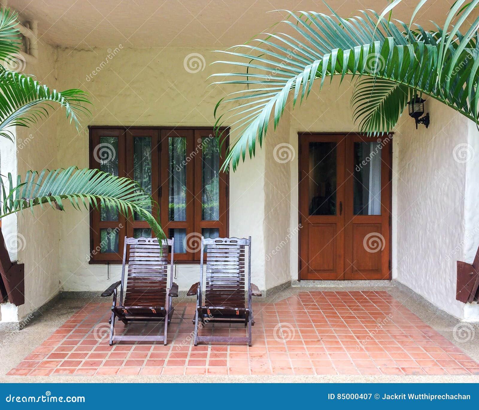 Paare von traditionellen hölzernen Klappstühlen auf Patio des Balkons oder Terrasse im offenen Gebiet vor Windows und Türen für e