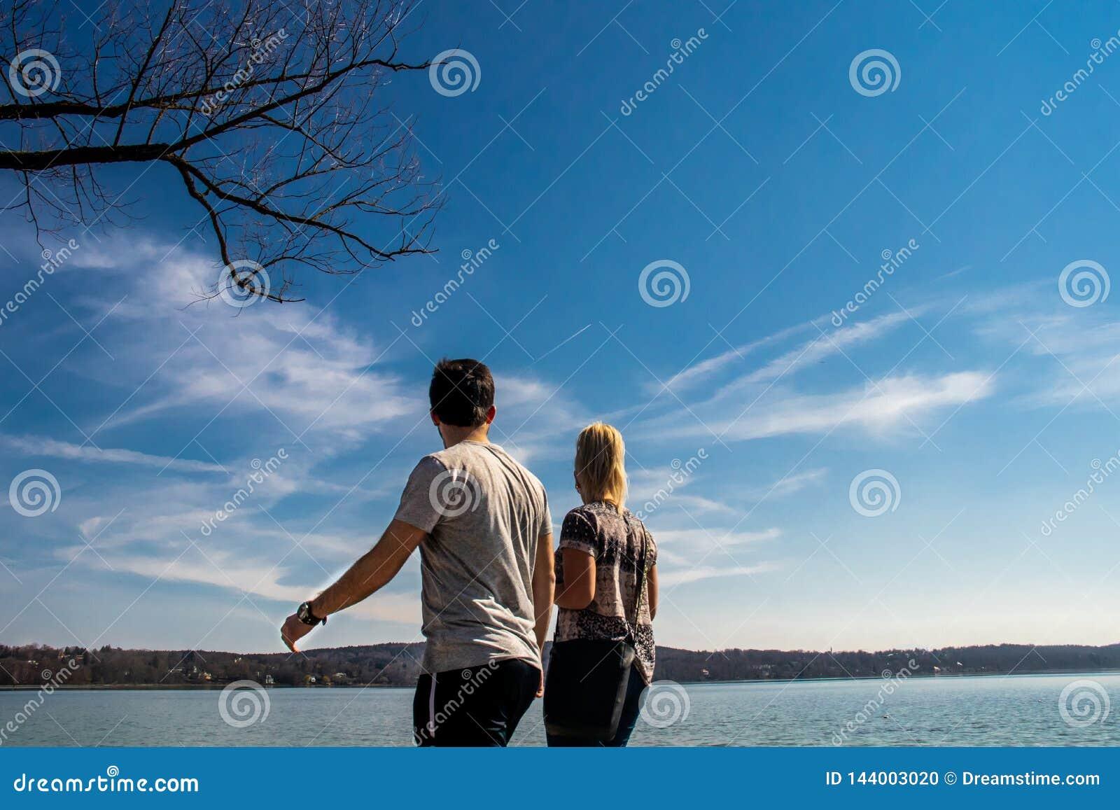 Paare, welche die schöne Seelandschaft mit klarem Hintergrund des blauen Himmels in Starnberg, Deutschland betrachten