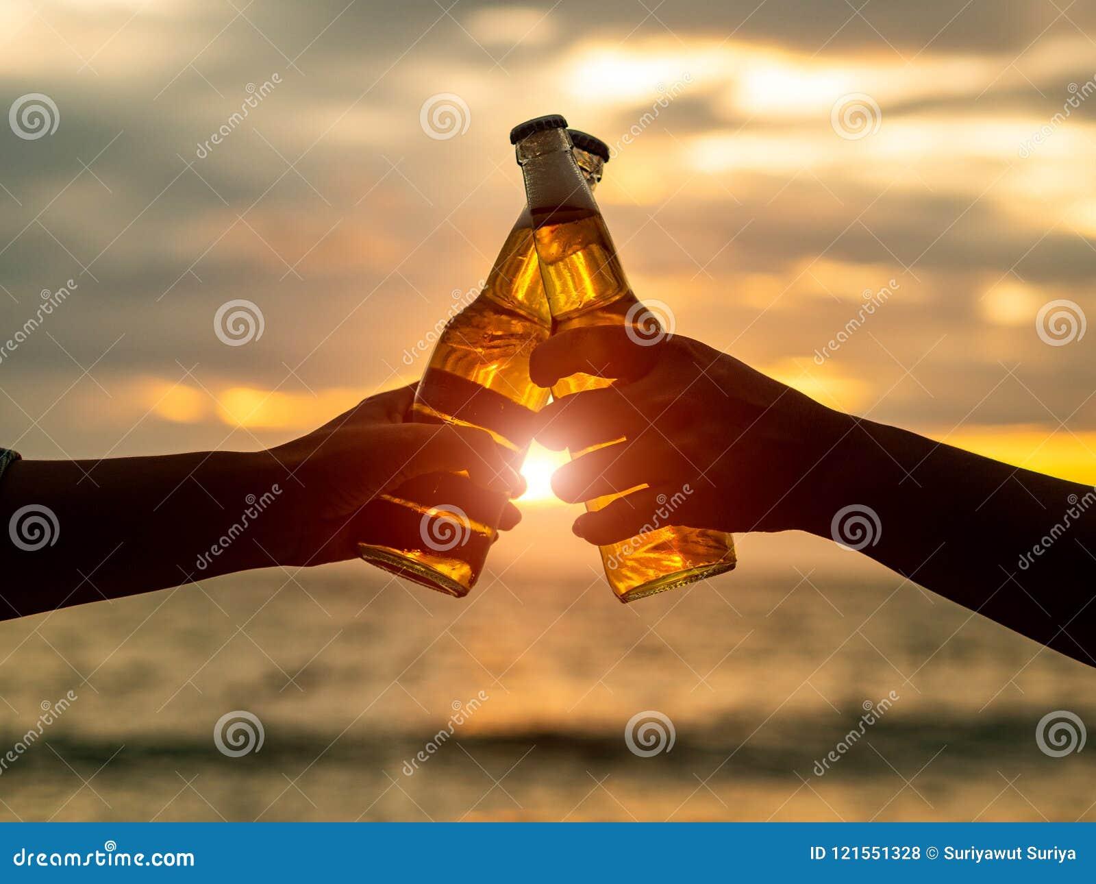 Paarhanden die bierflessen houden en op zonsondergangbea klinken