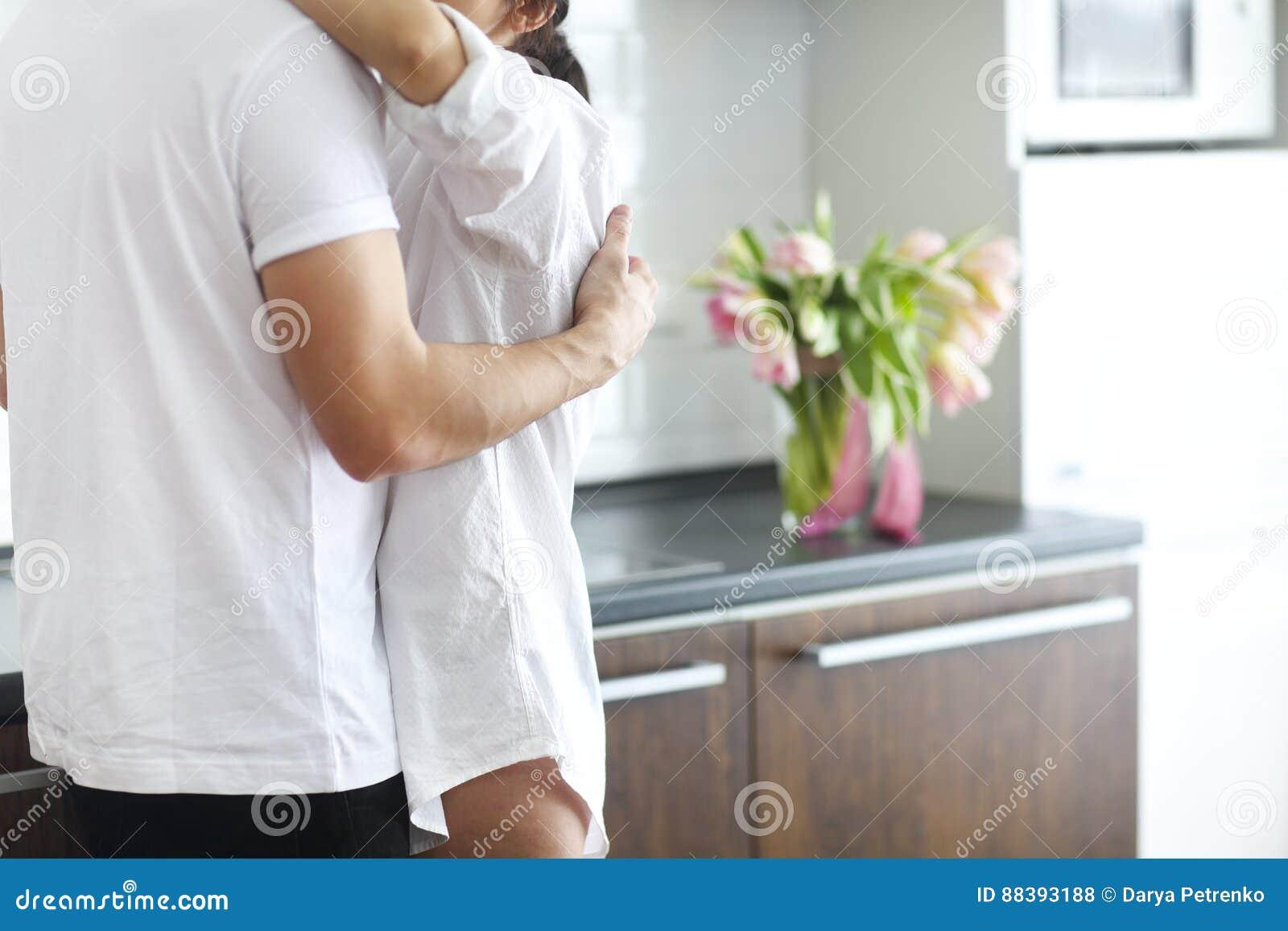 Paarkussen en omhelzingen bij keuken in de ochtend