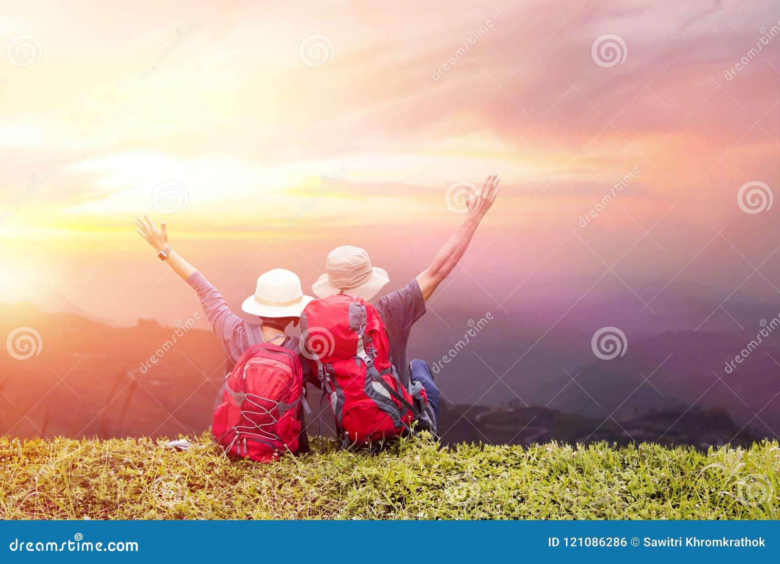 Paarrugzak die van zonsondergang op piek van mistige berg genieten