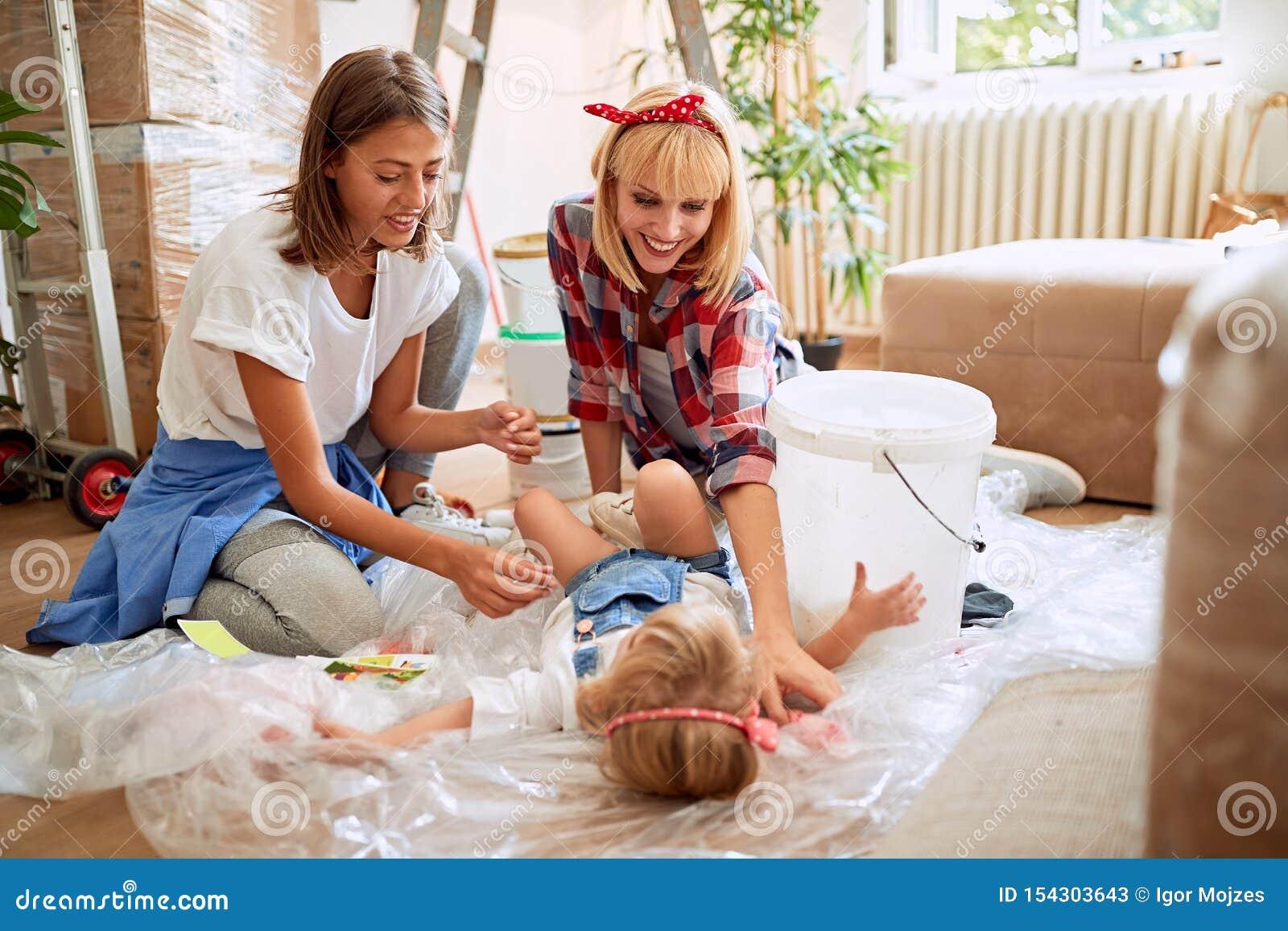 Paarvrouwen die zich in nieuw huis bewegen en pret met een peutermeisje hebben