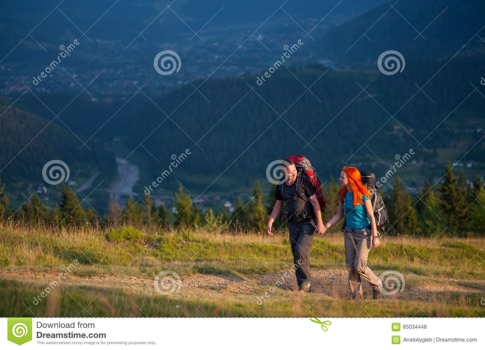 Paarwandelaars die met rugzakken handen houden, die in de bergen lopen